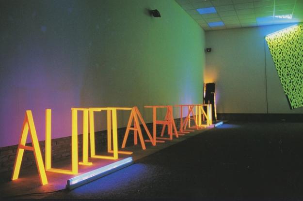 Autocanibalización Emulsion naranja fluorescente y luz negra Letras en madera 50 x 70 cm 2002 Museo Gustavo de Maeztu, 2002