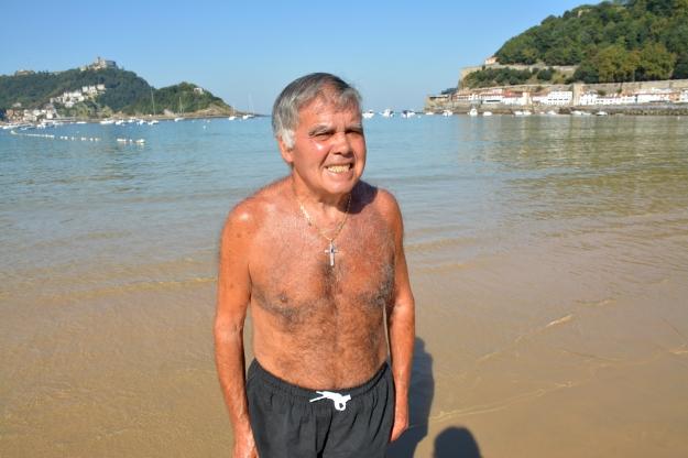 hombre con cruz y pecho perlado en la playa